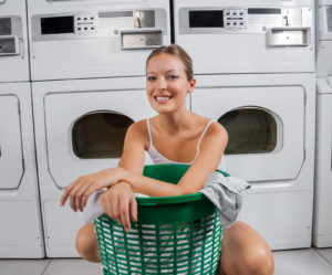 Portrait of beautiful woman with clothes basket in laundry